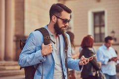 有充分的胡子和理发的,佩带的便衣和太阳镜游人,举行一个背包和发短信在a 库存照片