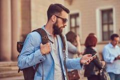有充分的胡子和理发的,佩带的便衣和太阳镜游人,举行一个背包和发短信在a 免版税图库摄影