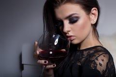 有充分的嘴唇明亮的构成的美丽的性感的甜女孩坐有一杯的沙发在一件黑晚礼服的酒 库存照片