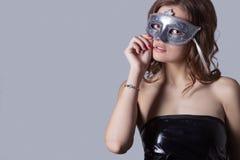 有充分的嘴唇的美丽的性感的女孩在黑皮革礼服戴着一个灰色面具,欢乐图象 免版税库存照片