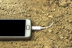 有充电器的白色智能手机被塞住入沙子 被弄脏的前面和后面背景 免版税库存照片