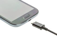 有充电器缆绳的宏观智能手机 免版税库存图片