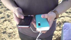 有充电您的智能手机的小配件的年轻人 股票视频