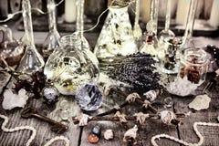有光、五角星形、水晶、淡紫色花和礼节对象的不可思议的瓶在巫婆桌上 库存照片