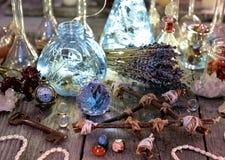 有光、五角星形、水晶和仪式对象的不可思议的瓶在巫婆桌上 图库摄影