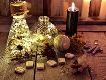 有光、诗歌和黑蜡烛的不可思议的瓶在巫婆桌上 免版税库存图片