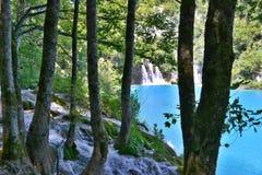 有光亮天蓝色色水和瀑布的湖 免版税库存图片