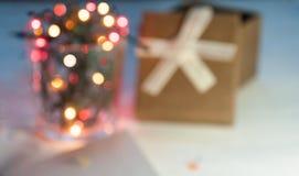 有光和一个礼物盒的圣诞节诗歌选有在轻的背景的一张空白的明信片的 圣诞节礼品 非常模糊 免版税库存照片