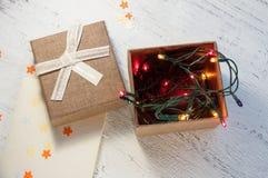 有光和一个礼物盒的圣诞节诗歌选有在轻的背景的一张空白的明信片的 圣诞节礼品 免版税库存图片