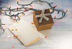 有光和一个礼物盒的圣诞节诗歌选有在轻的背景的一张空白的明信片的 圣诞节礼品 库存图片