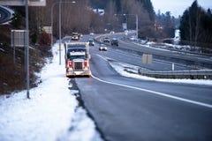 有光的大半船具卡车在冬天多雪的highwa路旁  库存图片