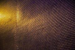 有光的现代砖墙在城市 免版税库存图片