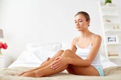 有光秃的腿的美丽的妇女在床上在家 免版税库存图片