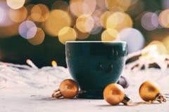 有光bokeh的咖啡杯和与被弄脏的背景圣诞节概念的金黄球 免版税图库摄影