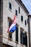 有克罗地亚旗子的美丽的老房子在主要走的街道上在老镇杜布罗夫尼克 免版税库存照片