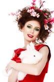 有兔宝宝、蛋和花春天复活节概念的妇女 免版税图库摄影
