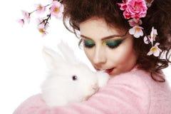 有兔宝宝、蛋和花春天复活节概念的妇女 免版税库存照片