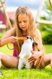 有兔宝宝宠物的愉快的孩子在家在庭院里 免版税库存图片