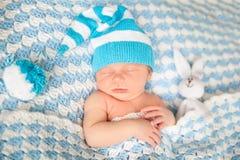 有兔宝宝的睡觉的新出生的婴孩在一条蓝色毯子戏弄 库存图片
