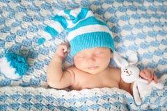 有兔宝宝的睡觉的新出生的婴孩在一条蓝色毯子戏弄 图库摄影