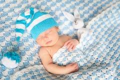 有兔宝宝的睡觉的新出生的婴孩在一条蓝色毯子戏弄 免版税图库摄影
