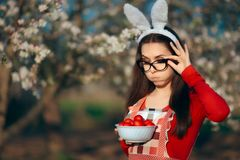 有兔宝宝耳朵、围裙和复活节彩蛋的滑稽的疲乏的主妇 图库摄影
