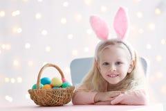 有兔宝宝耳朵和复活节彩蛋的逗人喜爱的滑稽的女孩 免版税库存图片