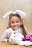 有兔宝宝耳朵和她逗人喜爱的白色兔子的愉快的小女孩 图库摄影