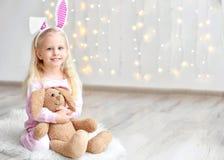 有兔宝宝耳朵和爱拥抱玩具的逗人喜爱的滑稽的女孩坐地板 库存图片