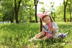 有兔宝宝耳朵的充分小女孩和篮子复活节彩蛋 库存照片