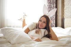 有兔宝宝耳朵的可爱的深色的女孩在她的头和说谎用在一张床上的咖啡在她的卧室舒适概念 库存图片