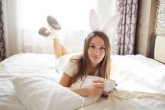 有兔宝宝耳朵的可爱的深色的女孩在她的头和说谎用在一张床上的咖啡在她的卧室 库存照片