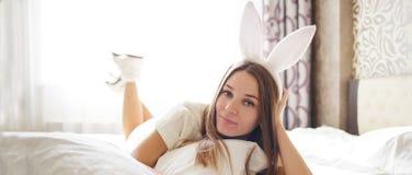 有兔宝宝耳朵的可爱的深色的女孩在她的头在床上躺在她的卧室 免版税库存照片