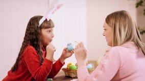 有兔宝宝耳朵的女孩在头,笑,做面孔和微笑,当她的母亲画笔复活节彩蛋时 股票录像