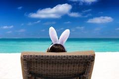 有兔宝宝耳朵的妇女在一个热带海滩 免版税库存照片