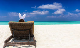有兔宝宝耳朵的妇女在海滩的太阳椅子 库存照片