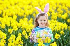 有兔宝宝耳朵的孩子在复活节彩蛋狩猎 免版税库存图片