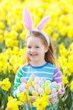 有兔宝宝耳朵的孩子在复活节彩蛋狩猎 免版税库存照片