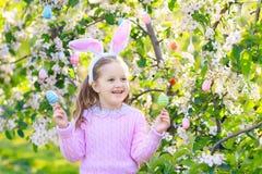 有兔宝宝耳朵的孩子在庭院复活节彩蛋狩猎 库存图片