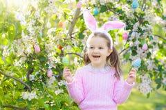 有兔宝宝耳朵的孩子在庭院复活节彩蛋狩猎 免版税库存图片
