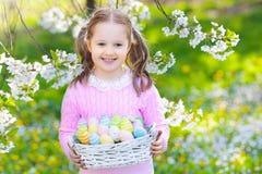 有兔宝宝耳朵的孩子在庭院复活节彩蛋狩猎 库存照片