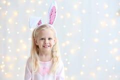 有兔宝宝耳朵的逗人喜爱的滑稽的女孩在背景 库存照片