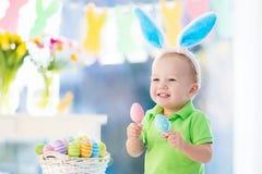 有兔宝宝耳朵的婴孩在复活节彩蛋狩猎 免版税库存图片