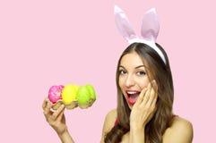 有兔宝宝耳朵藏品的愉快的惊奇的妇女怂恿看在桃红色背景的纸盒五颜六色的复活节彩蛋照相机 复制温泉 库存照片