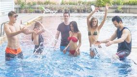 有党和跳舞在游泳池-时尚的朋友  免版税库存照片