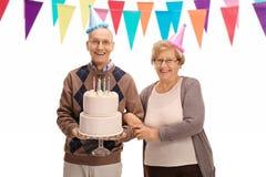 有党帽子和生日蛋糕的愉快的前辈 免版税库存照片