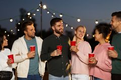 有党杯子的朋友在屋顶在晚上 库存图片