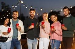 有党杯子的朋友在屋顶在晚上 图库摄影