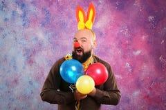 有党装饰、气球和兔宝宝耳朵的滑稽的肥胖人 免版税图库摄影