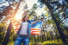 有全国美国国旗的愉快的微笑的少妇户外 图库摄影